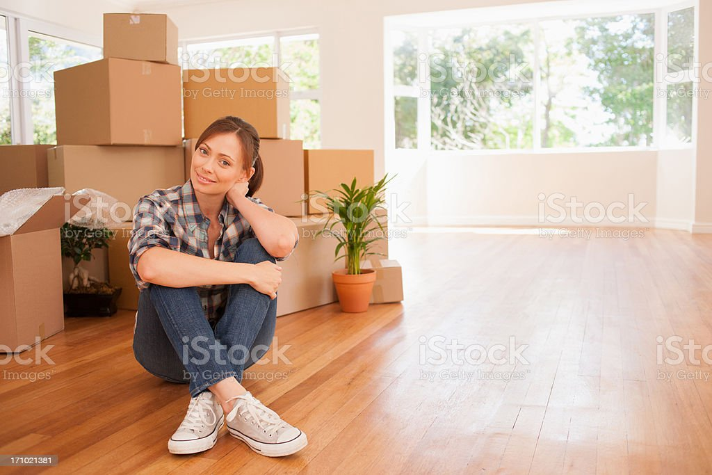 Woman sitting on floor of new house stock photo