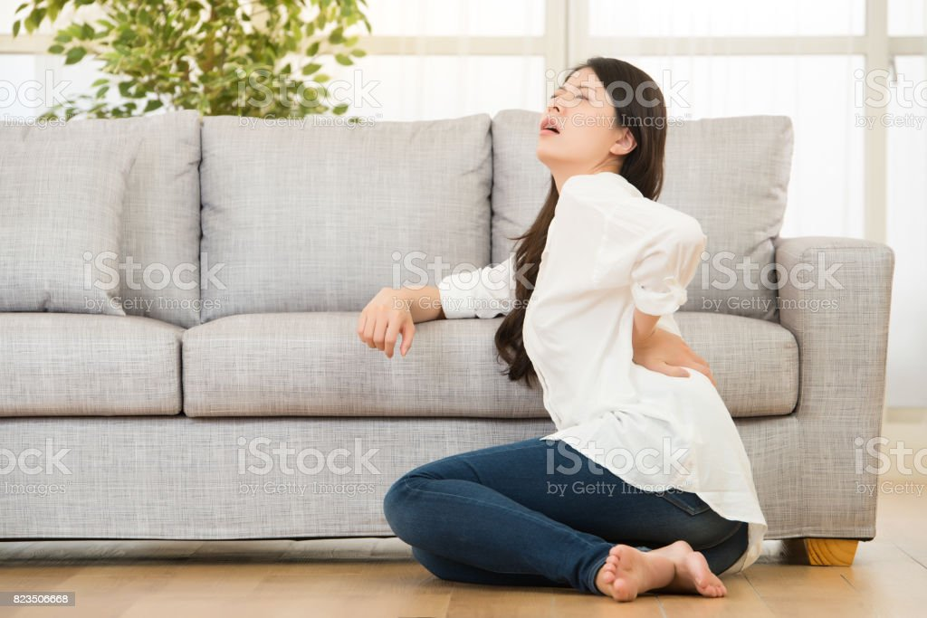 Woman sitting on floor touching her back stock photo