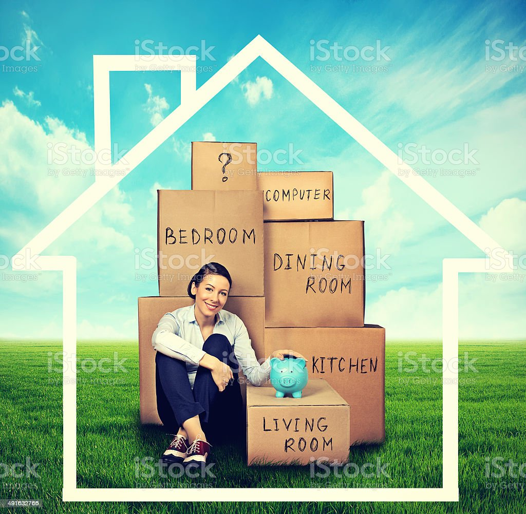 woman sitting on green meadow with many boxes stock photo