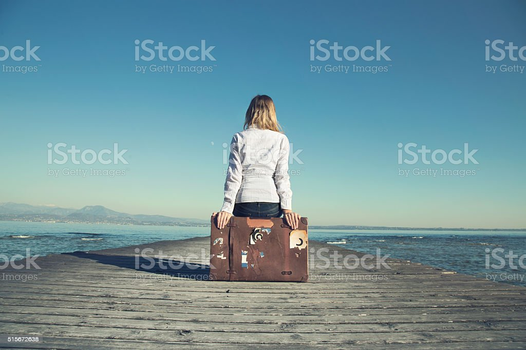 woman sitting on her suitcase waiting for the sunset stock photo