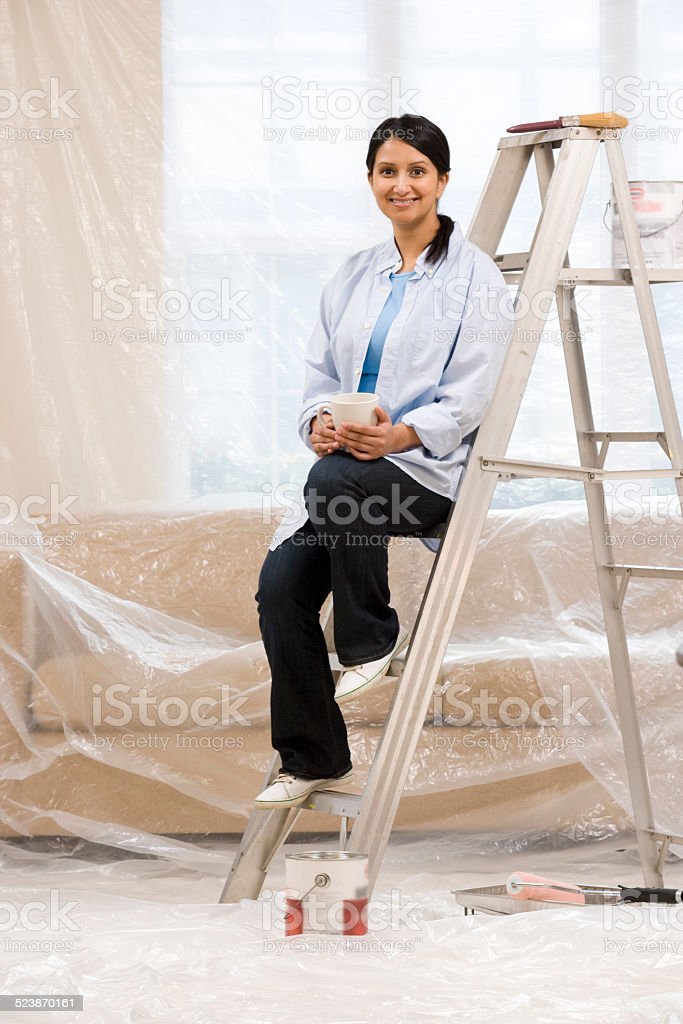 Woman Sitting on Ladder With Paint Supplies stock photo