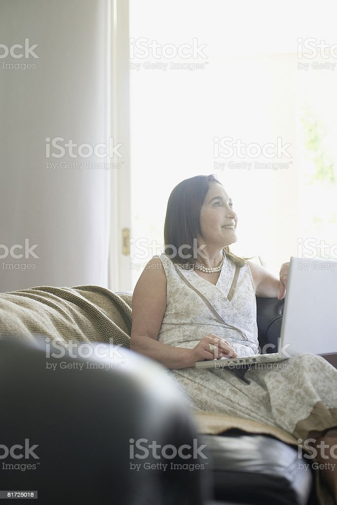 Woman sitting on living room sofa with laptop smiling royalty-free stock photo