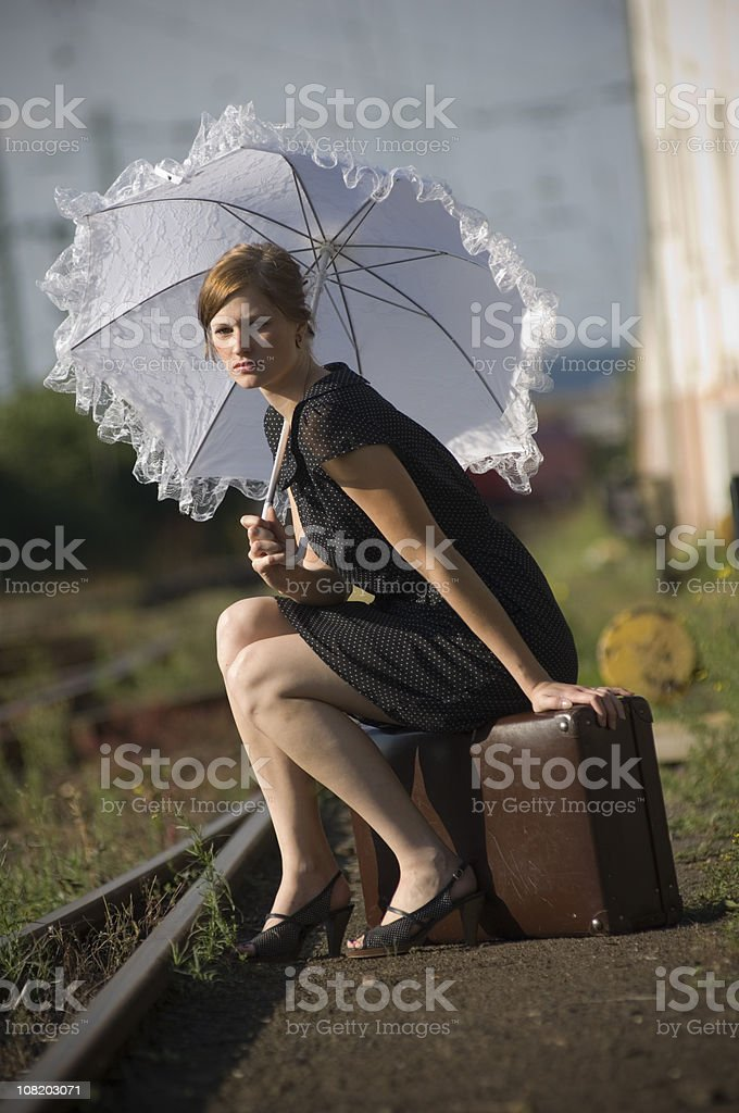 Woman Sitting on Luggage Near Train Tracks and Carrying Parasol royalty-free stock photo