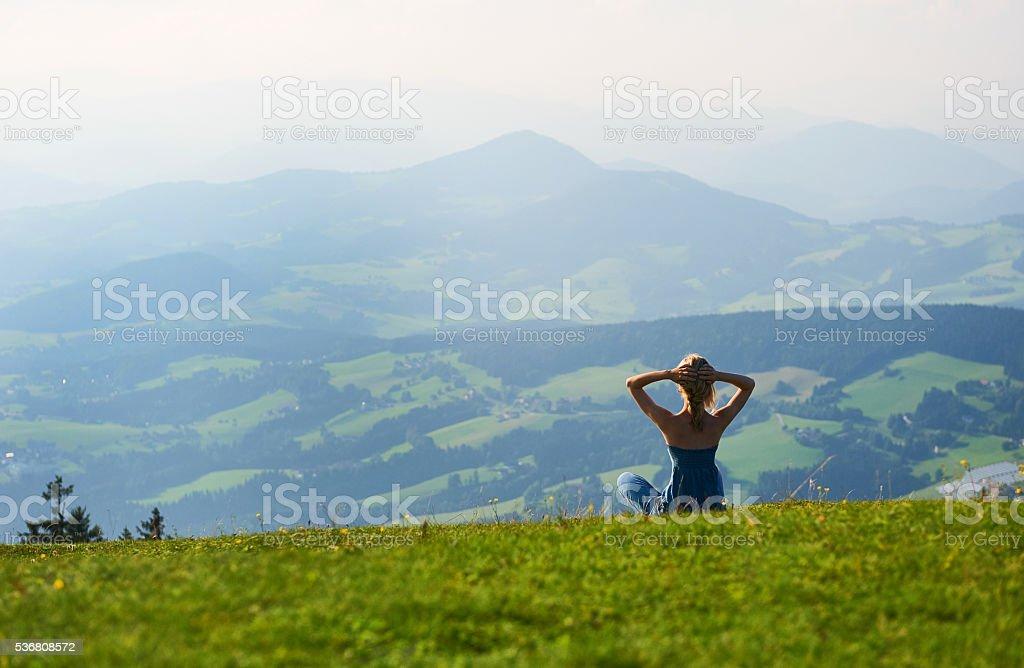 Woman sitting on mountain top stock photo