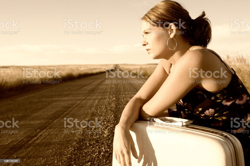 Woman Sitting on Open Road, Waiting royalty-free stock photo