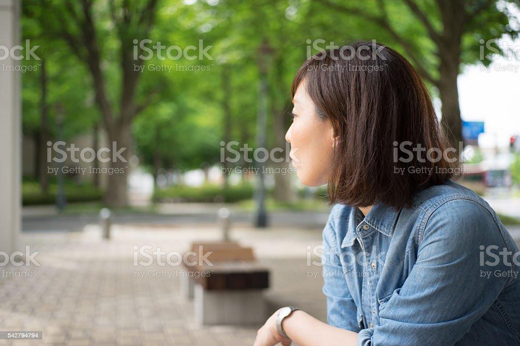 Femme assise sur le banc en plein air photo libre de droits