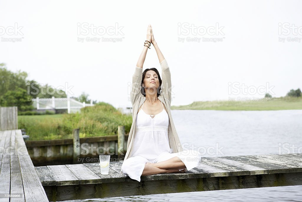 Woman sitting on pier, stretching arms royalty-free stock photo