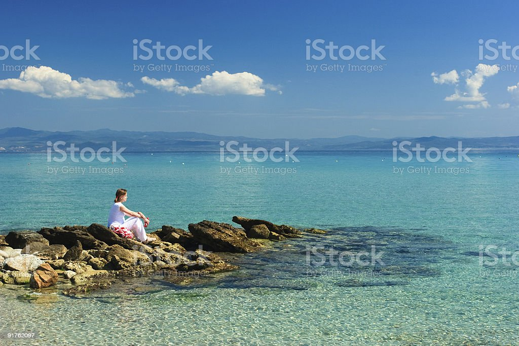 Woman sitting on rocks by blue tropical ocean royalty-free stock photo