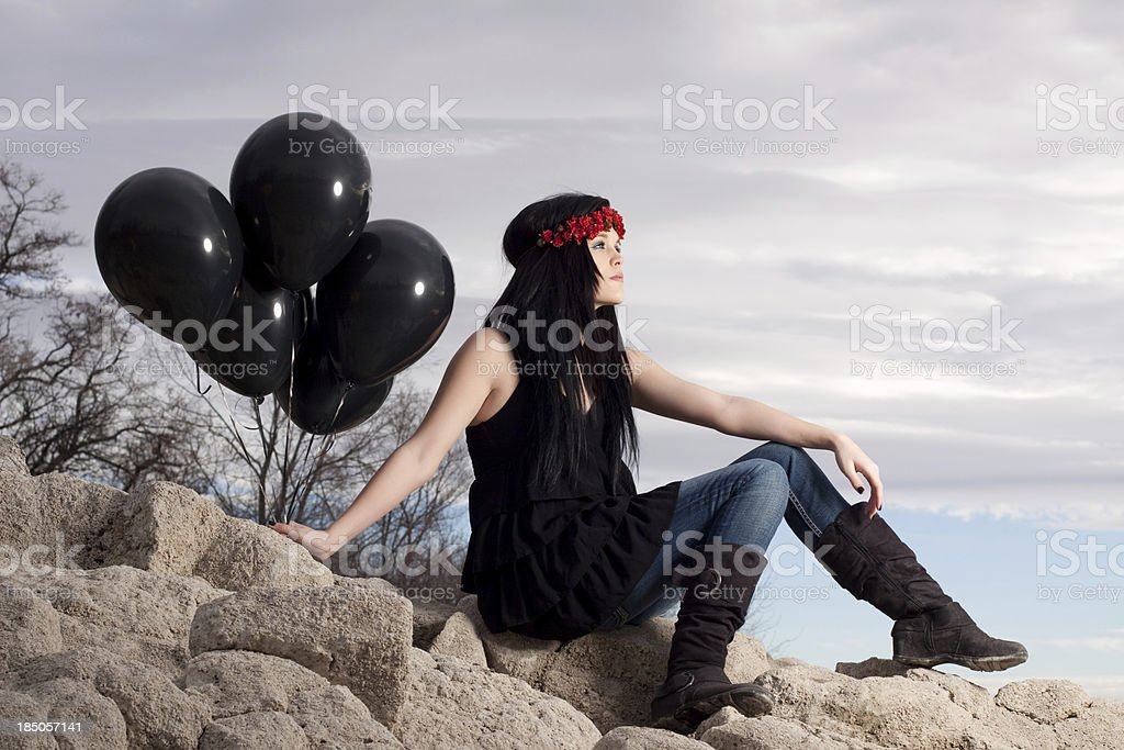 Frau sitzt auf einem Felsen in der Natur Holding Ballons – Foto