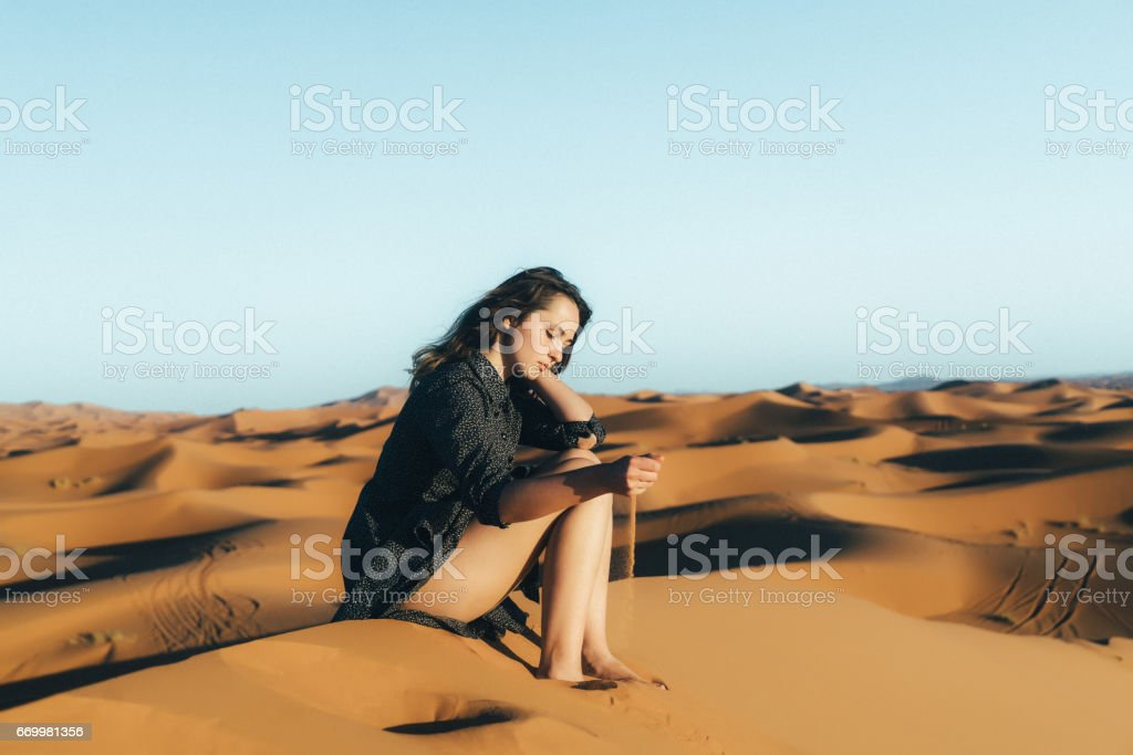 Woman sitting on sand   in the desert stock photo