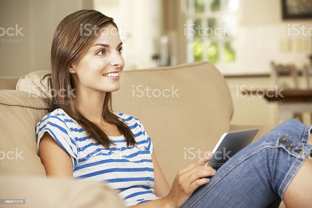 Woman Sitting On Sofa At Home Using Tablet Computer royalty-free stock photo