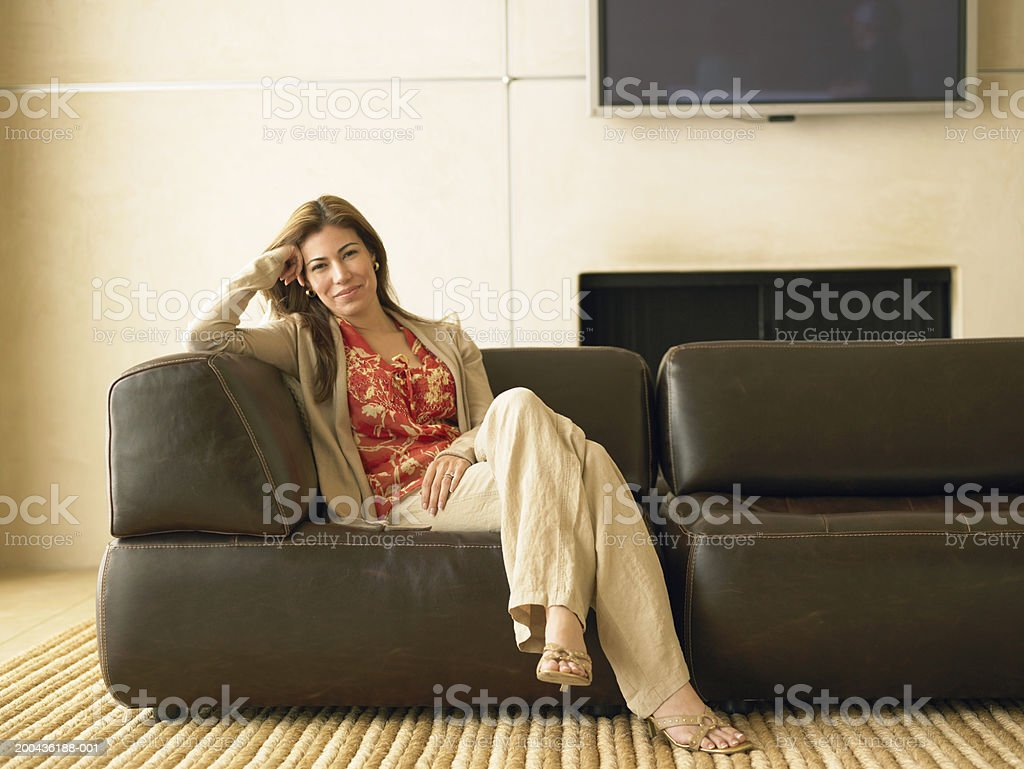 Woman sitting on sofa in living room, portrait stock photo