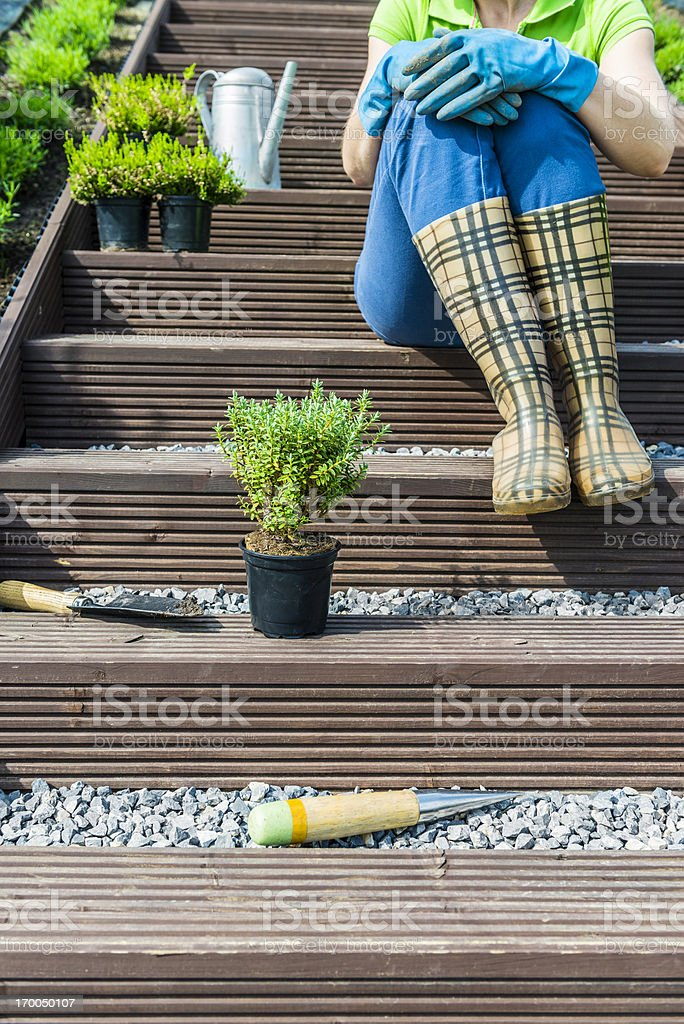 Woman sitting on stairs in garden, resting after gardening works royalty-free stock photo