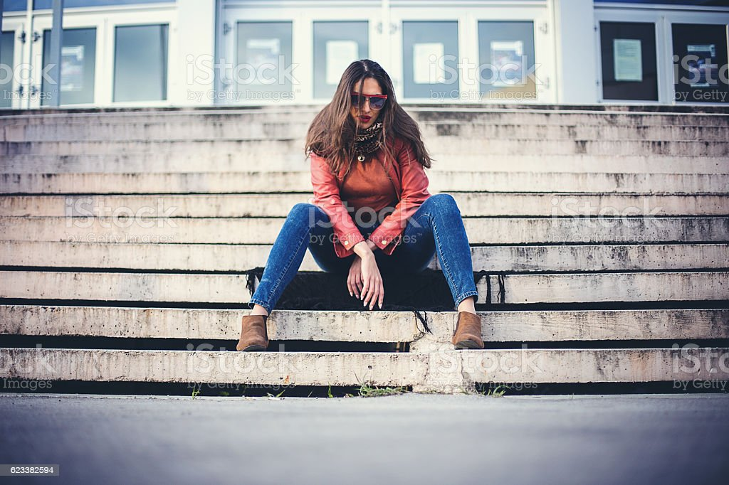 Woman sitting on stairs in the city stock photo