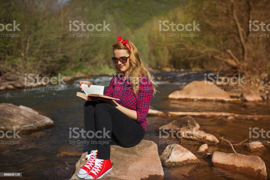 Woman sitting on stone and reading a book stock photo