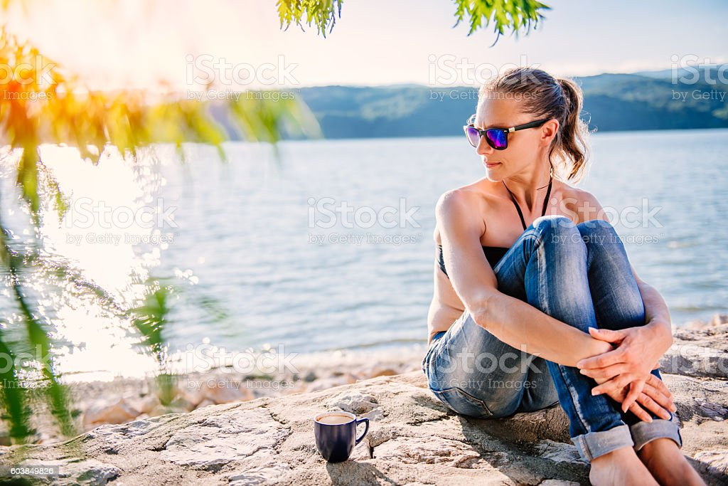 Woman sitting on stone dock and looking sideways stock photo
