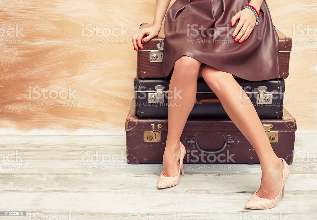 Woman sitting on suitcases stock photo