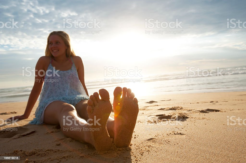 Woman sitting on the beach at sunrise royalty-free stock photo