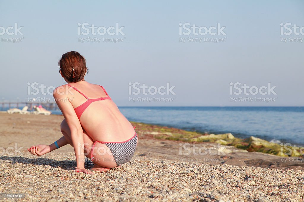 Woman sitting on the beach stock photo