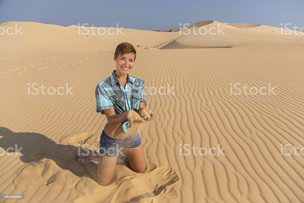 woman sitting on the beach with sand in hands stock photo