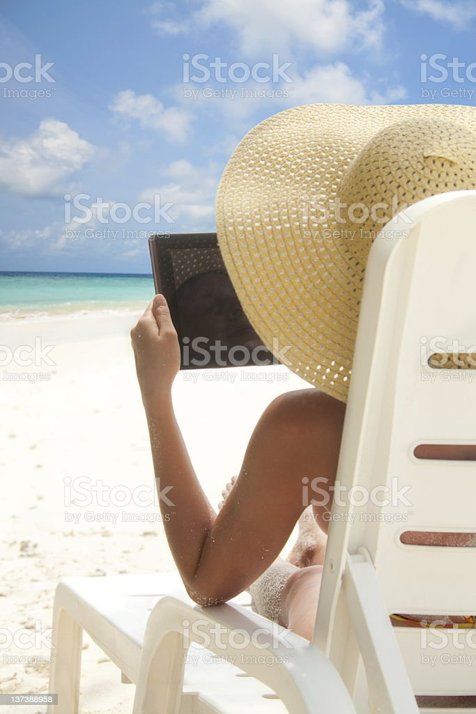 Woman sitting on the beach with tablet computer royalty-free stock photo