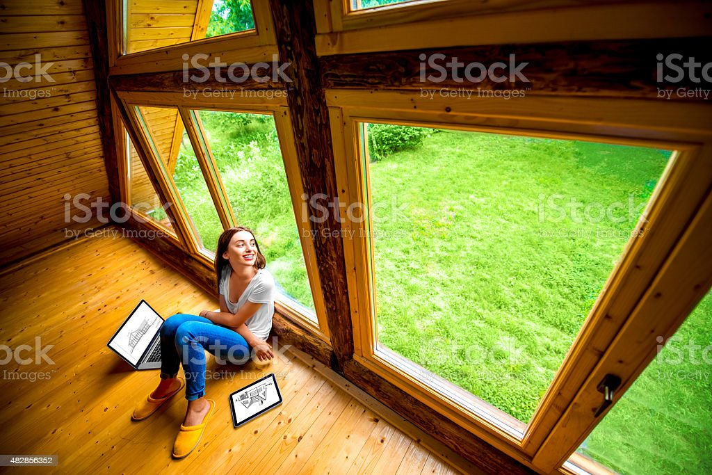Woman sitting on the floor in wooden house stock photo