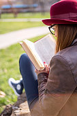 woman sitting on the grass and reading the book