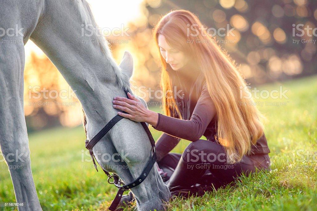 Woman sitting on the ground stroking a feeding white horse stock photo