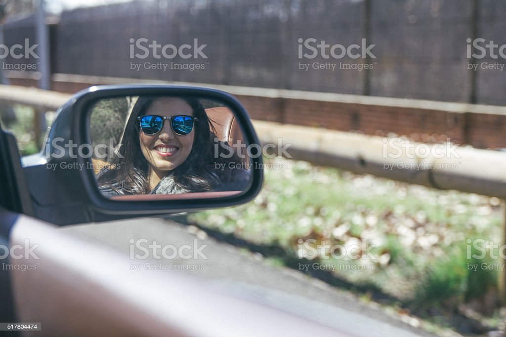 Woman sitting on the passenger seat of a convertible car stock photo