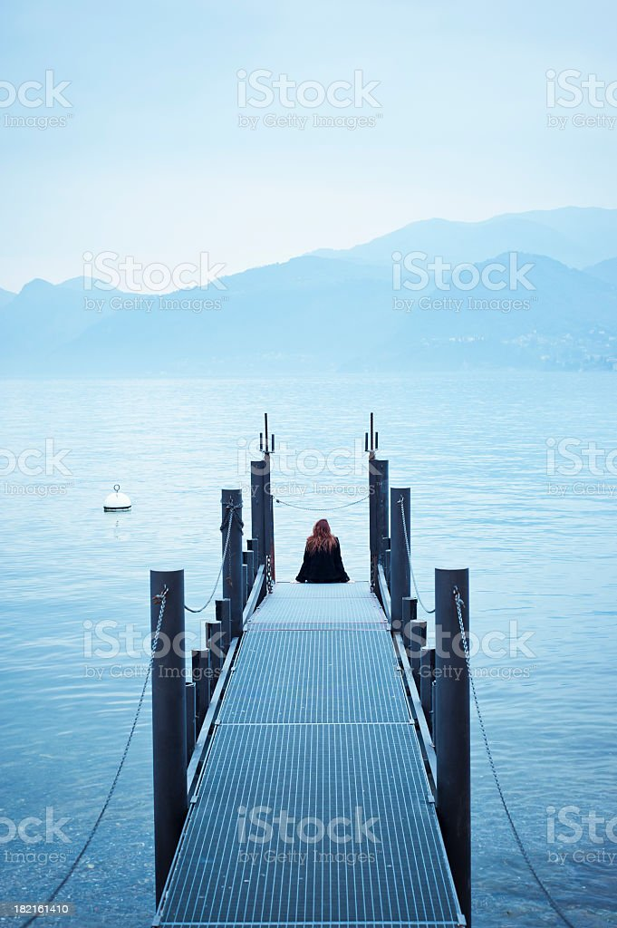 Woman Sitting On The Pier In Lake Como royalty-free stock photo