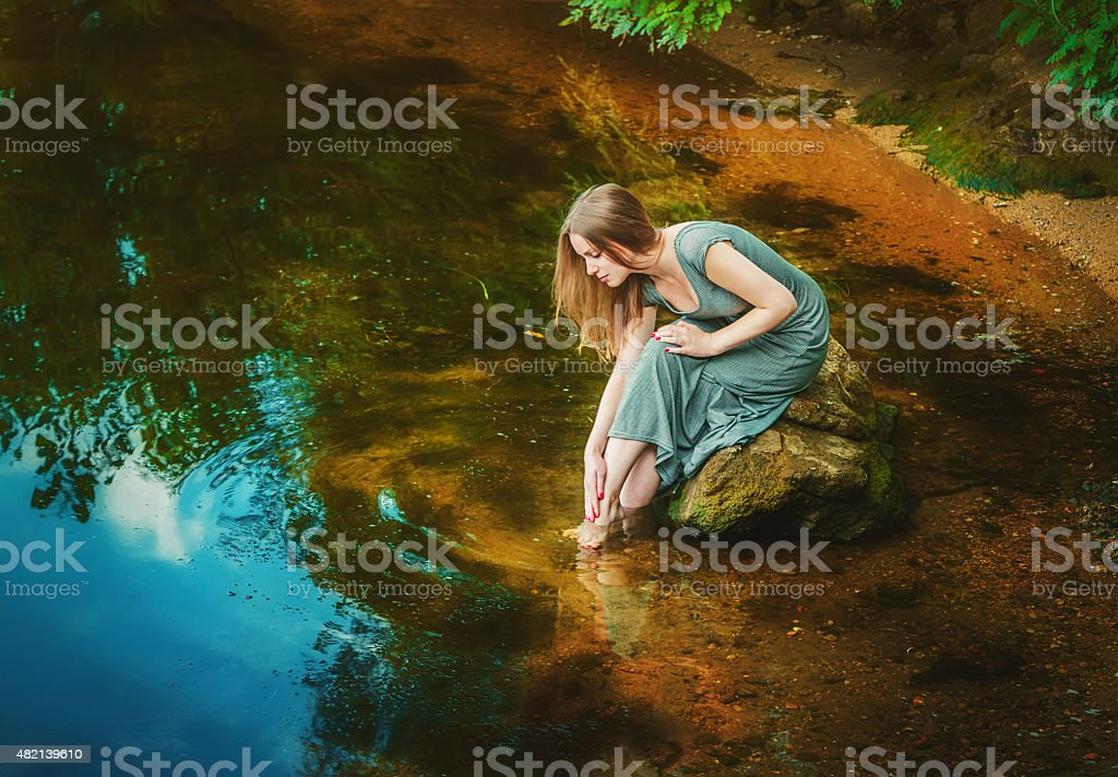 Woman sitting on the rock in a pond stock photo