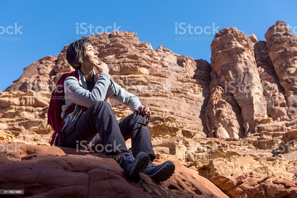 Woman sitting on the rock in Wadi Rum, Jordan stock photo