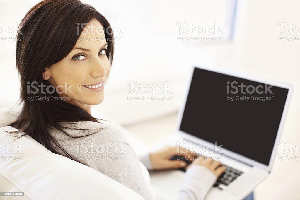 Woman sitting on the sofa using laptop royalty-free stock photo