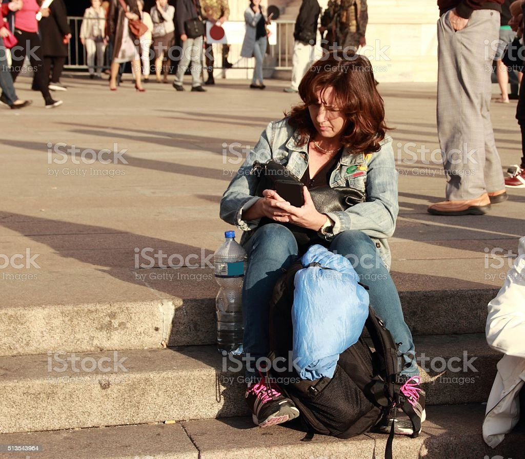Woman sitting on the stairs reading a message stock photo