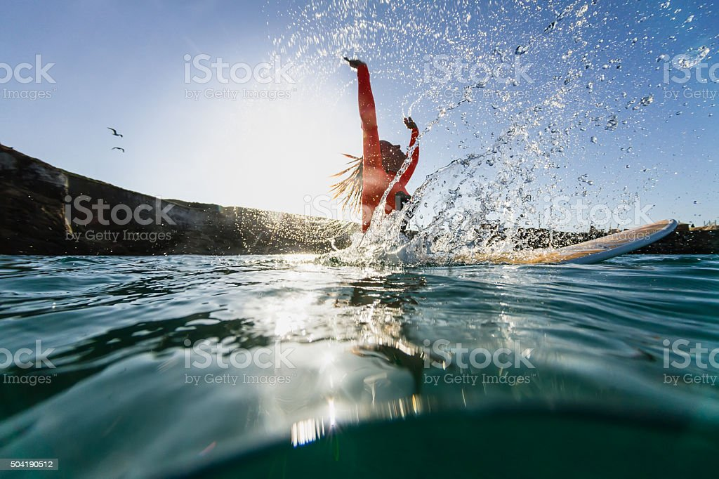 woman sitting on the surfboard and doing splashes stock photo