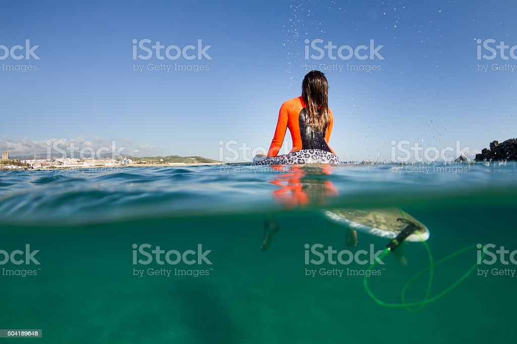 woman sitting on the surfboard in the water royalty-free stock photo