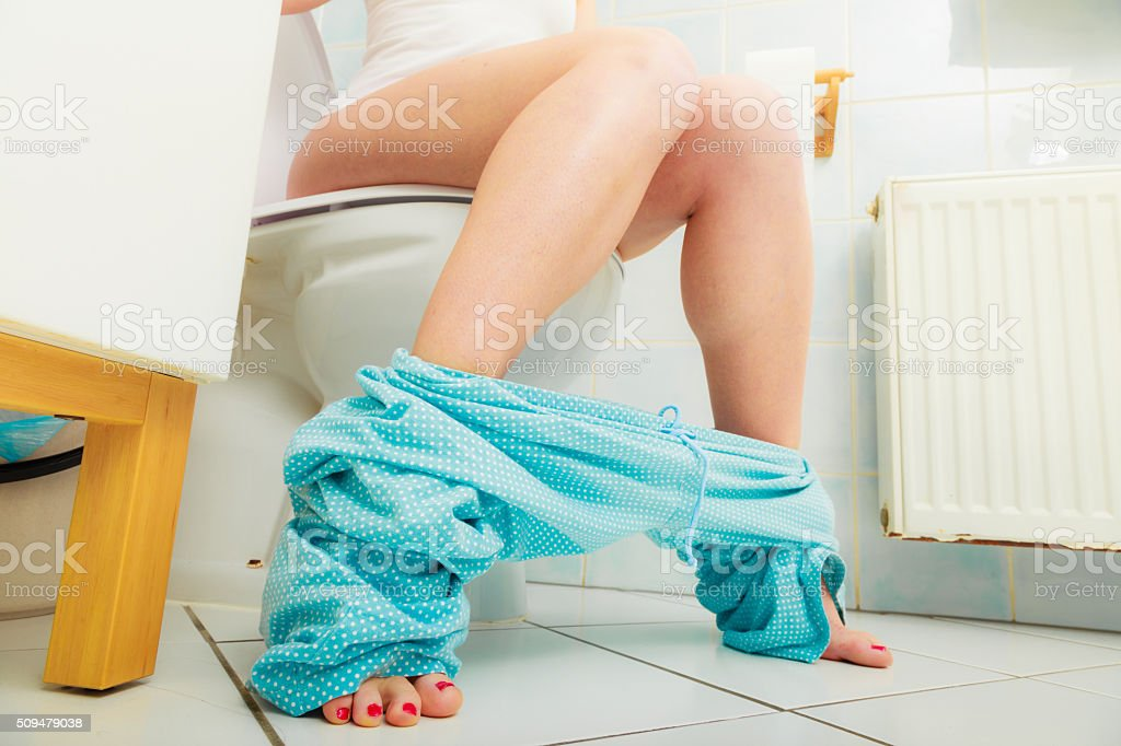 woman sitting on toilet in morning stock photo