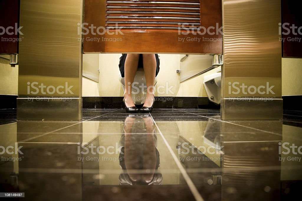 Woman Sitting on Toilet stock photo