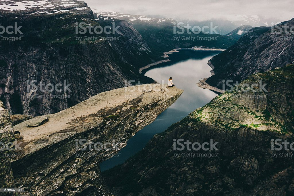 Woman sitting on Trolltunga stock photo