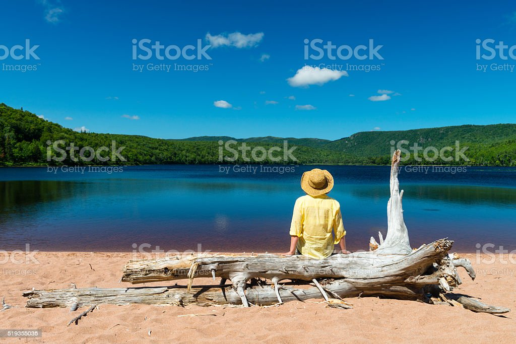 Woman sitting on trunk tree and looking at beautiful lake stock photo