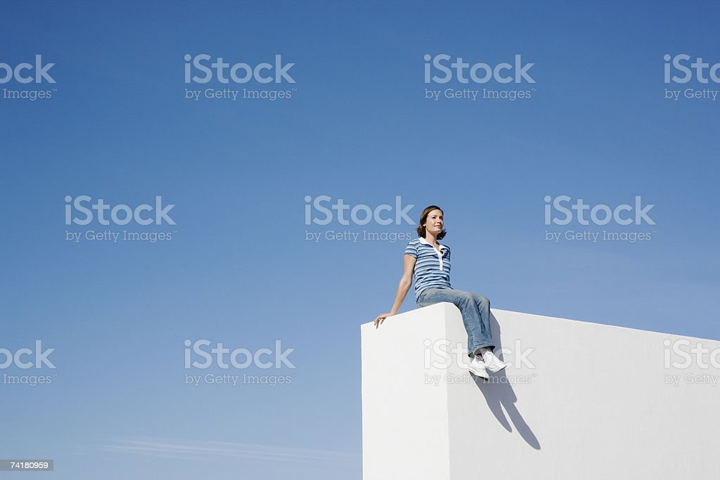 Woman sitting on wall outdoors with blue sky royalty-free stock photo