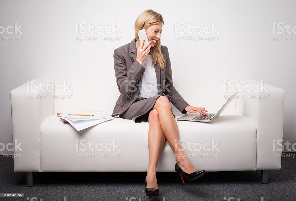 Woman sitting on white sofa and talking on the phone stock photo