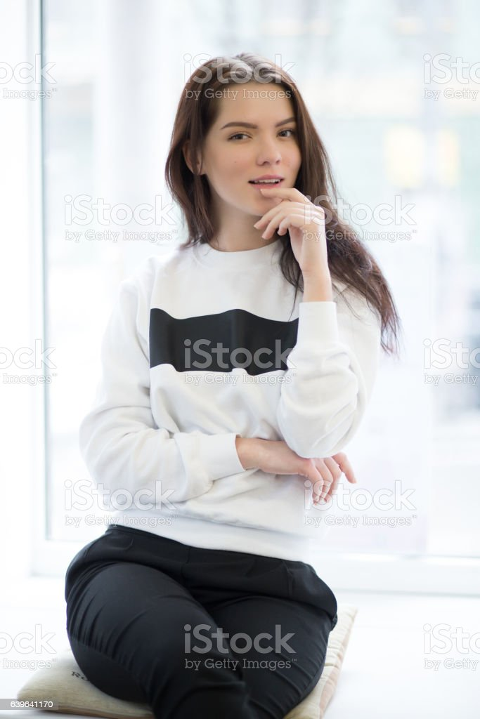 Woman sitting on windowsill in light room stock photo
