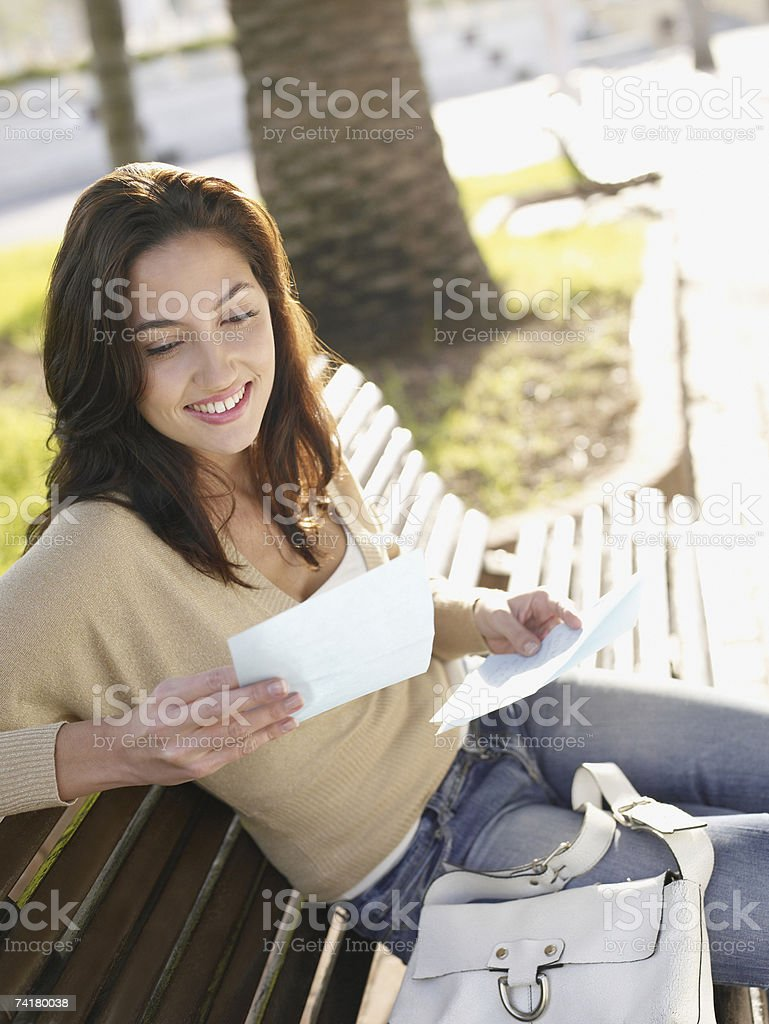 Woman sitting on wooden bench with personal letter smiling royalty-free stock photo