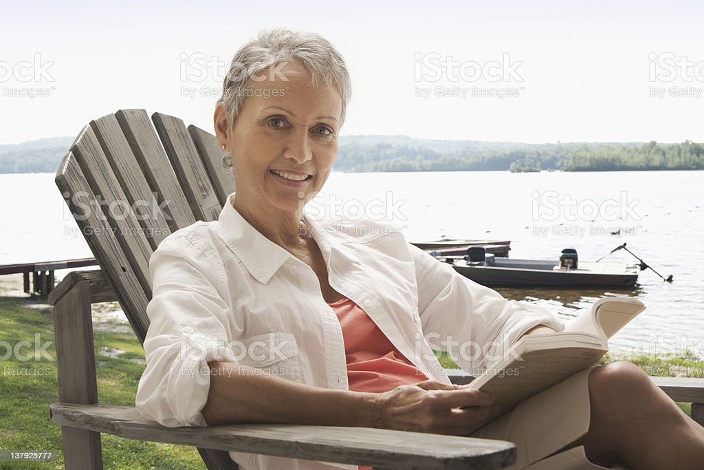 Woman sitting outdoor reading book stock photo