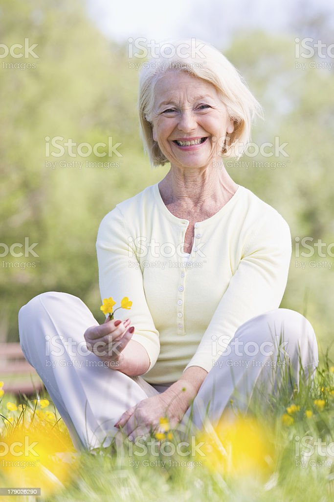 Woman sitting outdoors smiling and holding a Buttercup flower royalty-free stock photo