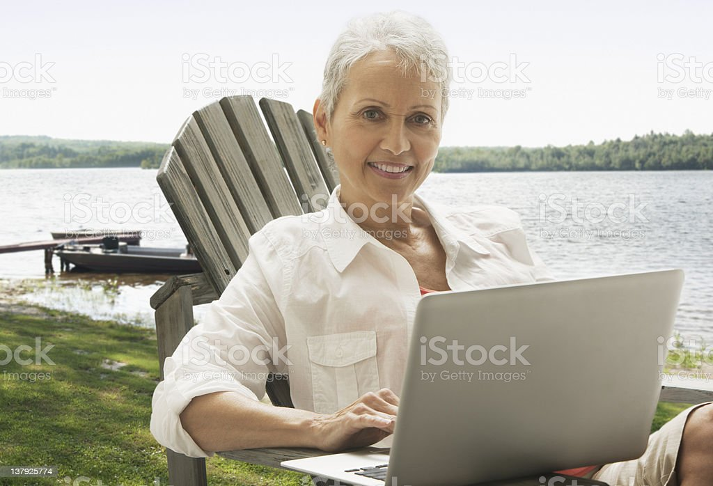 Woman sitting outdoors with laptop royalty-free stock photo