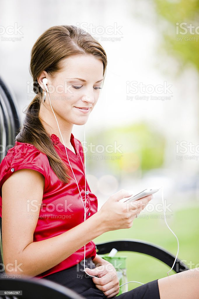 Woman sitting outside with her mp3 player royalty-free stock photo