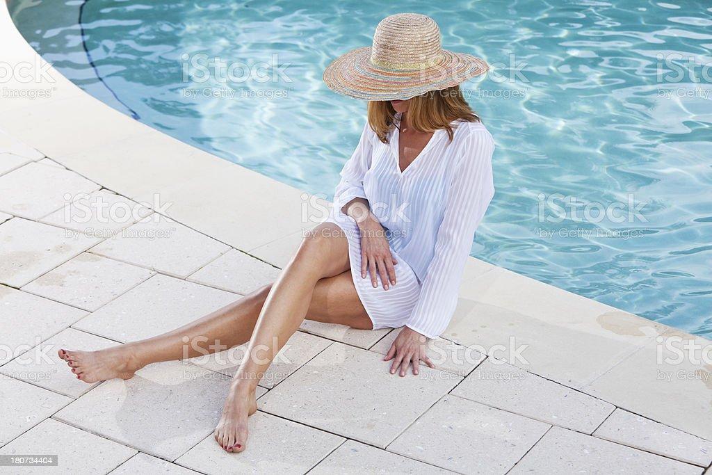 Woman sitting poolside stock photo