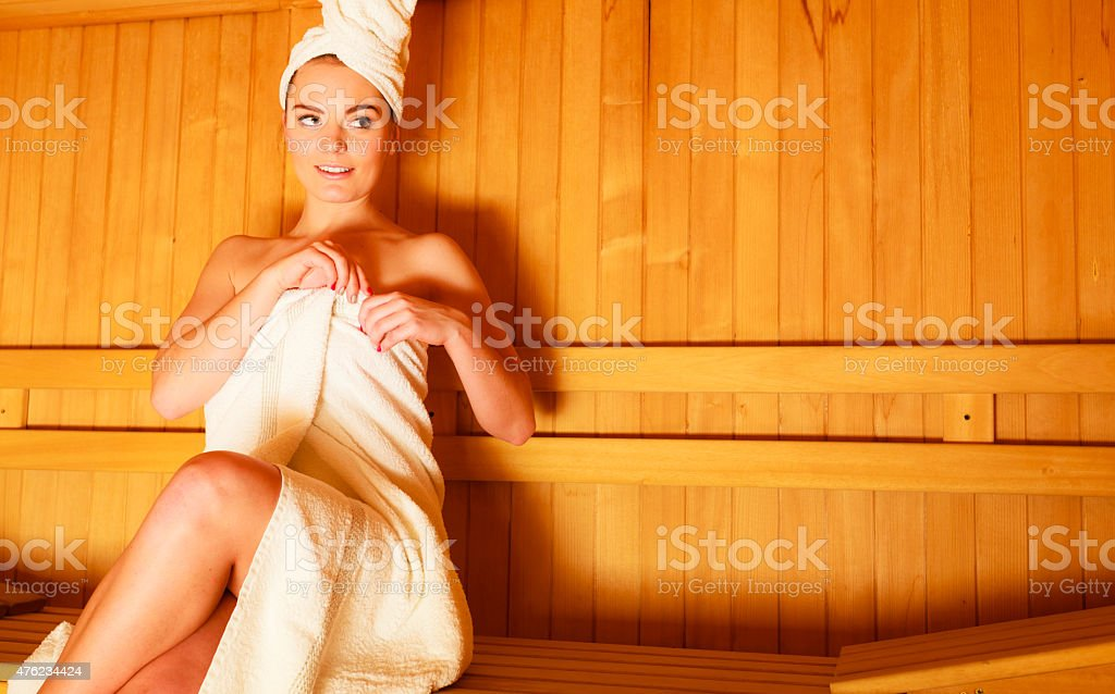 woman sitting relaxed in wooden sauna stock photo
